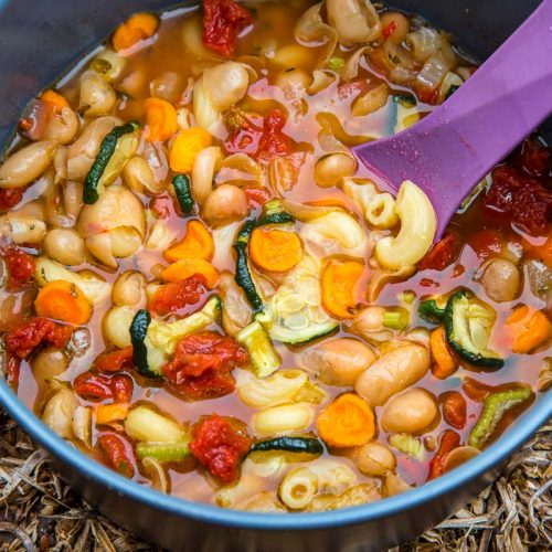 Minestrone in a grey backpacking pot with a purple spoon