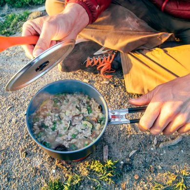 Dehydrated risotto in a backpacking pot. A man is lifting up the lid.
