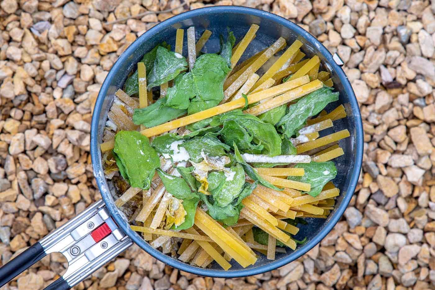 Pasta and dehydrated spinach in a backpacking pot