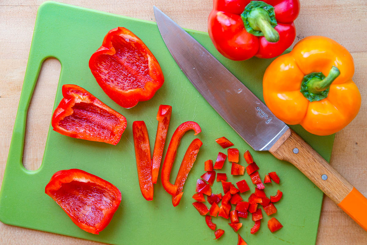 Sliced red bell peppers on a green cutting board