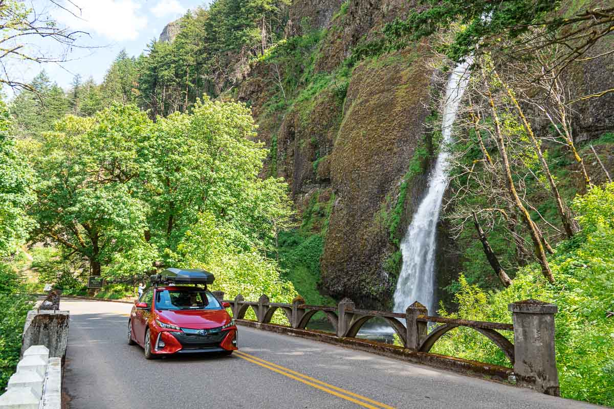 A red Prius Prime driving on a bridge next to a waterfall.