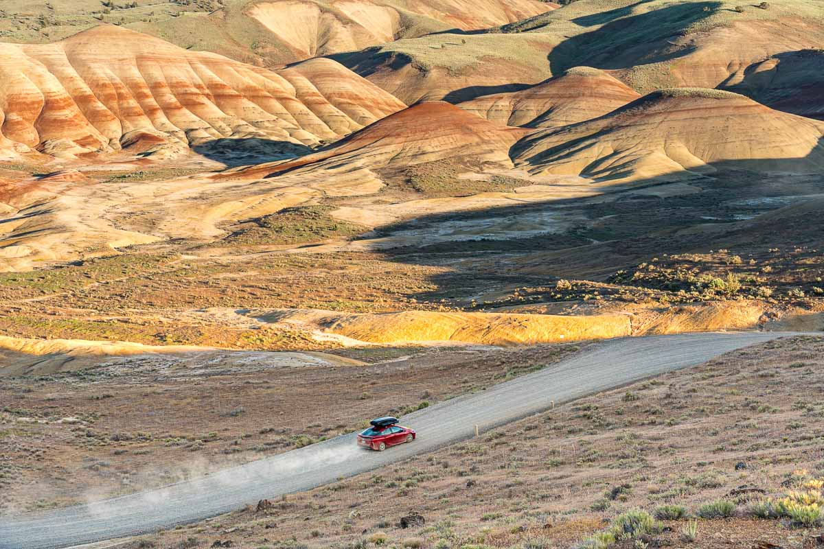 A red Prius Prime driving down a road towards the Painted Hills.