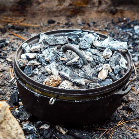 Dutch oven in a fire pit with embers on the lid