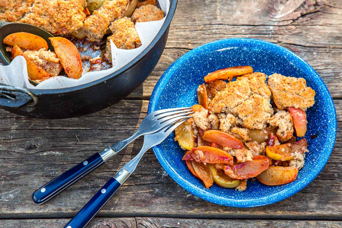 Apple cobbler in a blue bowl with two forks next to a Dutch oven