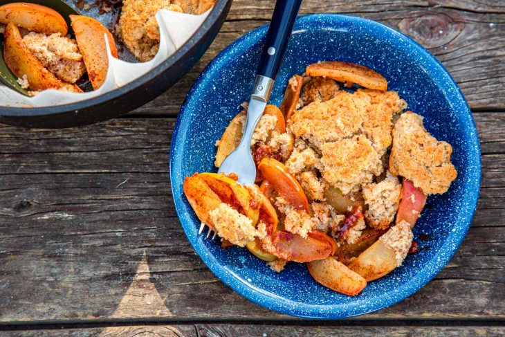 Apple cobbler in a blue bowl next to a Dutch oven