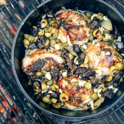 Chicken, green olives, and dried prunes in a Dutch oven in a fire pit