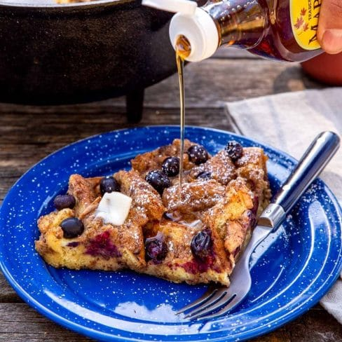 Maple syrup being drizzled over a slice of baked French toast.