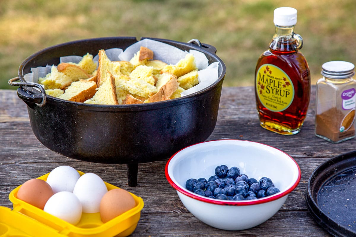 A dutch oven filled with torn bread, a bowl of blueberries, a yellow egg box with eggs, and a jug of maple syrup on a table.