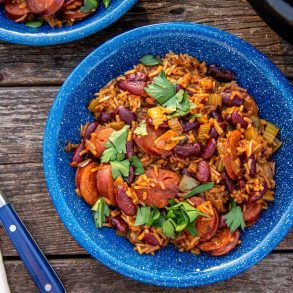 A blue bowl of red beans and rice on a natural surface