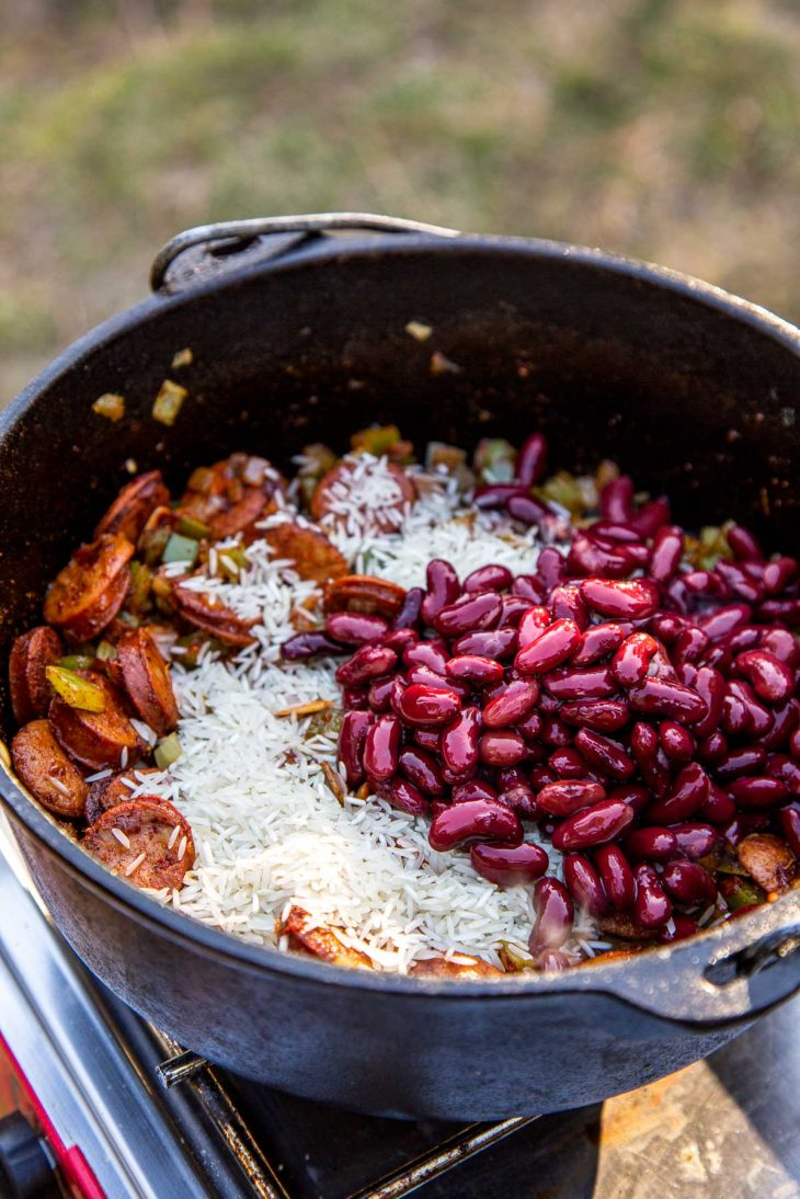 A dutch oven full of vegetables, beans, and rice sitting on a camp stove.