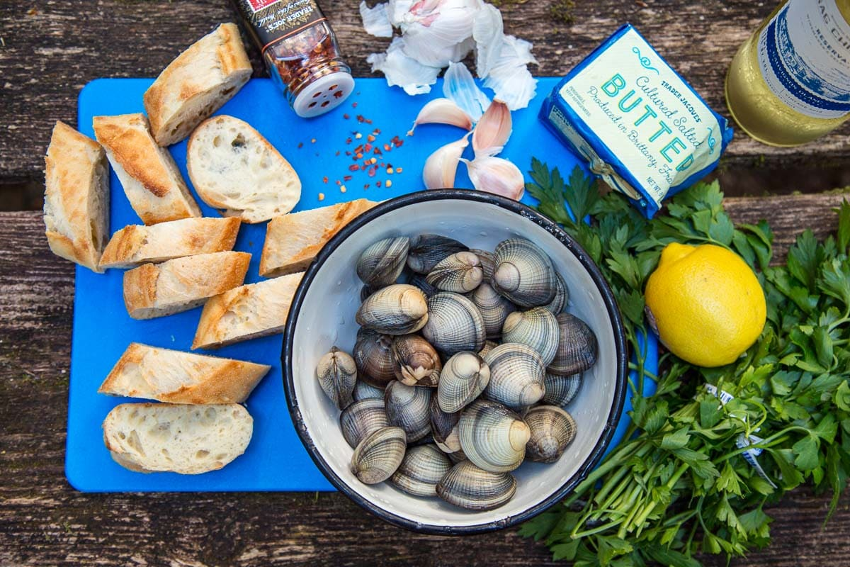 A table scene with a bowl of clams, sliced baguette, parsley, garlic cloves and a lemon on a cutting board