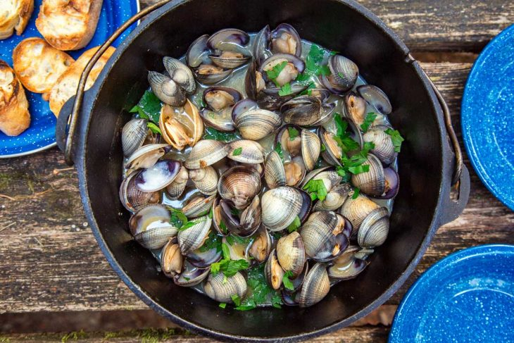 A Dutch oven filled with steamed clams on a table