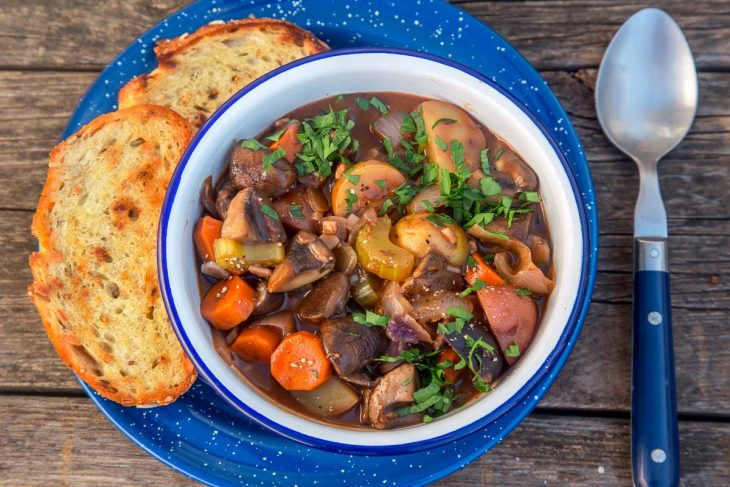 Vegetable stew in a blue and white bowl with grilled bread on the side