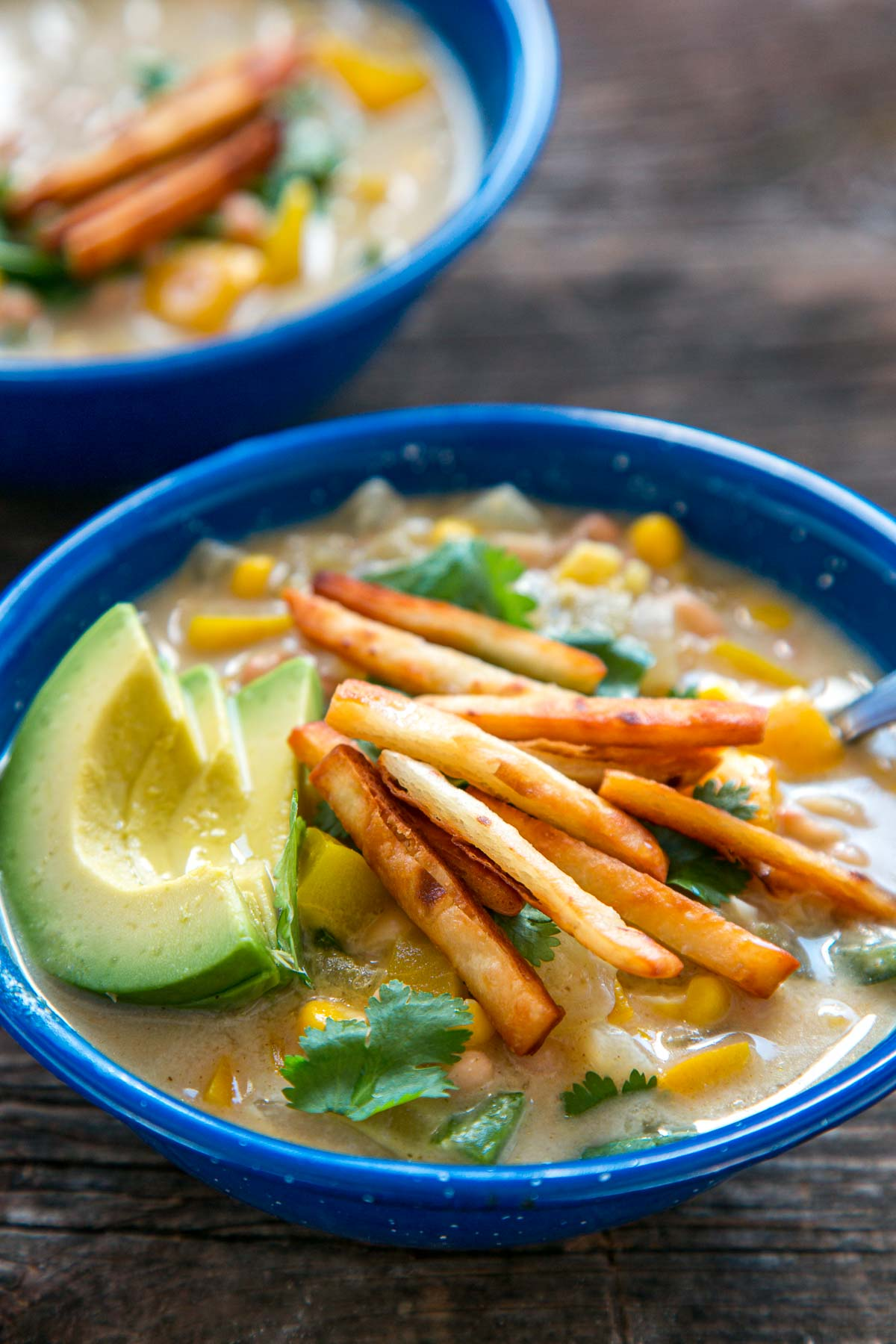 Two blue bowls of white bean chili on a table