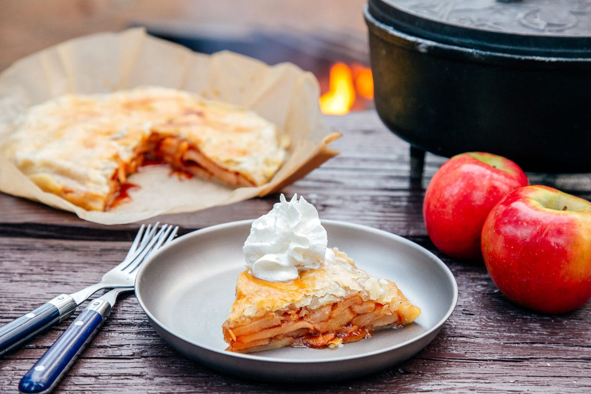 Slice of apple pie on a plate with a Dutch oven and campfire in the background