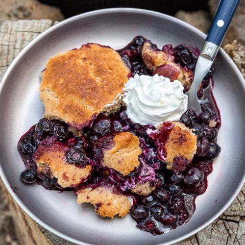 Blueberry cobbler and whipped cream on a plate