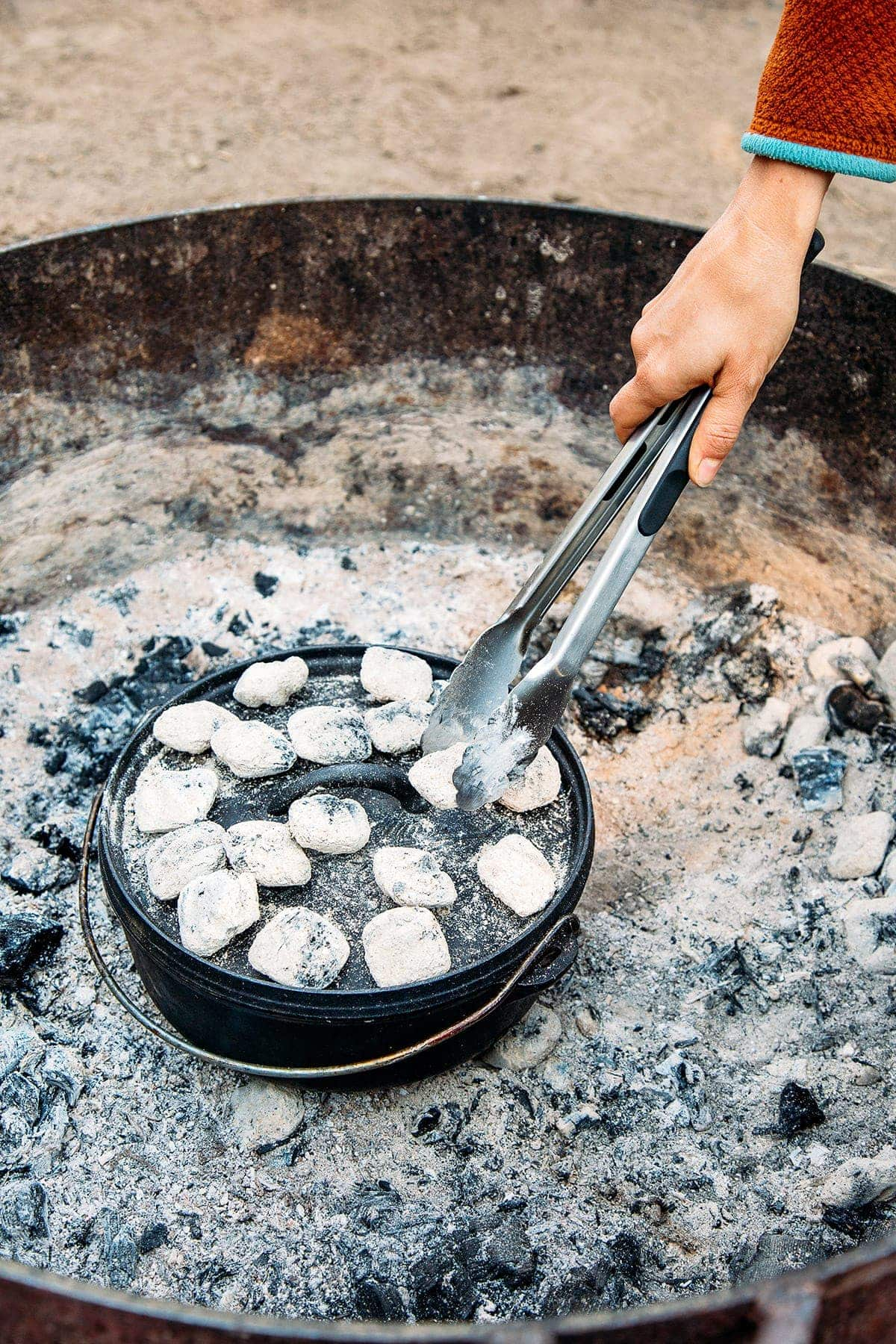 Woman adding coals to the top of a dutch oven in a campground fire pit.