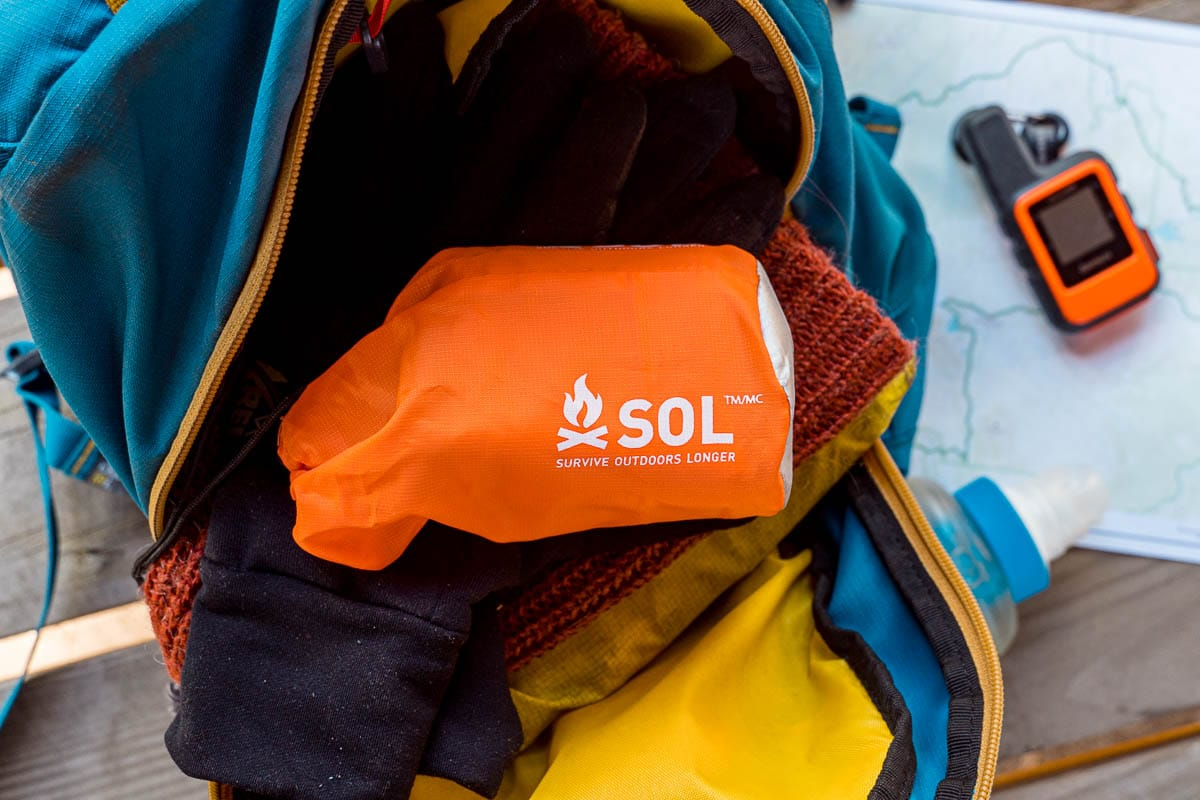 An orange bag containing an emergency bivy in a backpack