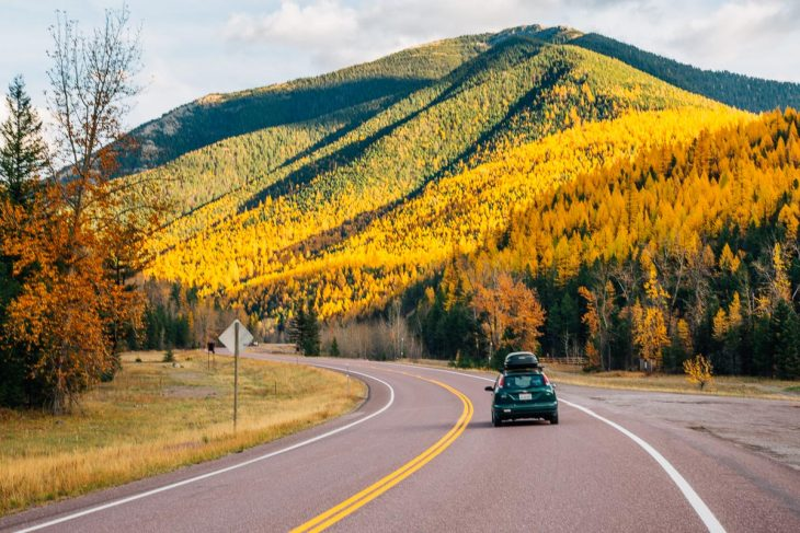 A car driving on a road with fall colors in the trees