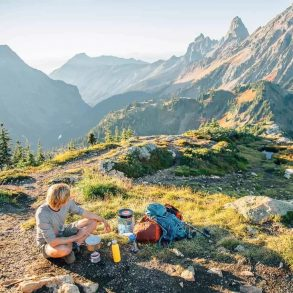 Michael sitting with his backpacking cooking kit and the Cascade mountains in the background
