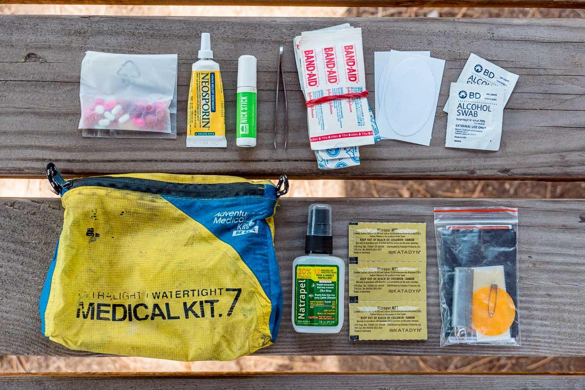 Contents of a hiking first aid kit laid out on a wood background