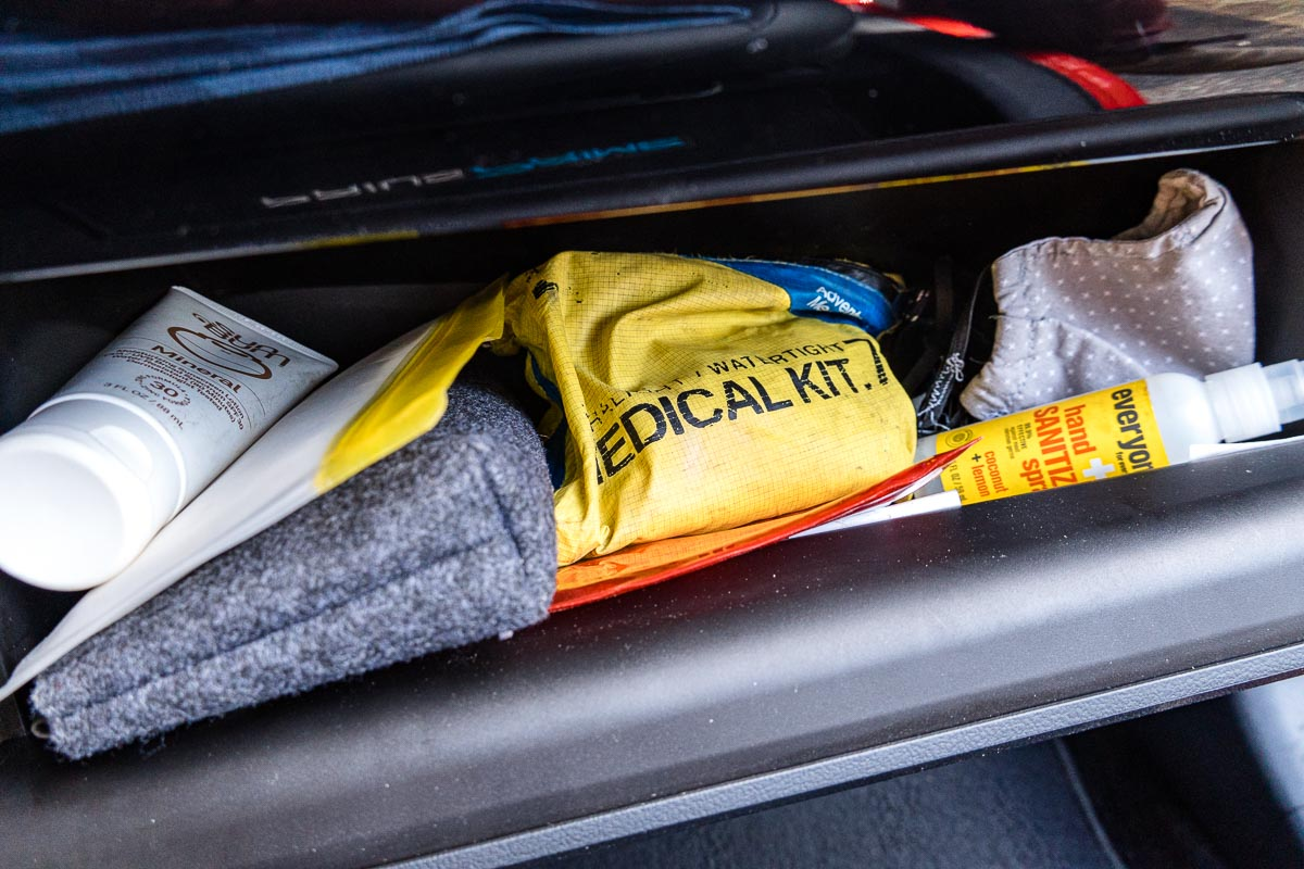 An open glove box with a first aid kit, hand sanitizer, sunscreen, and an organizing pouch