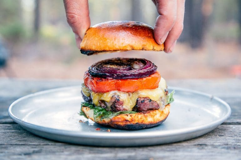 A man placing a bun on top of a grilled burger stacked with onions, tomatoes, and lettuce