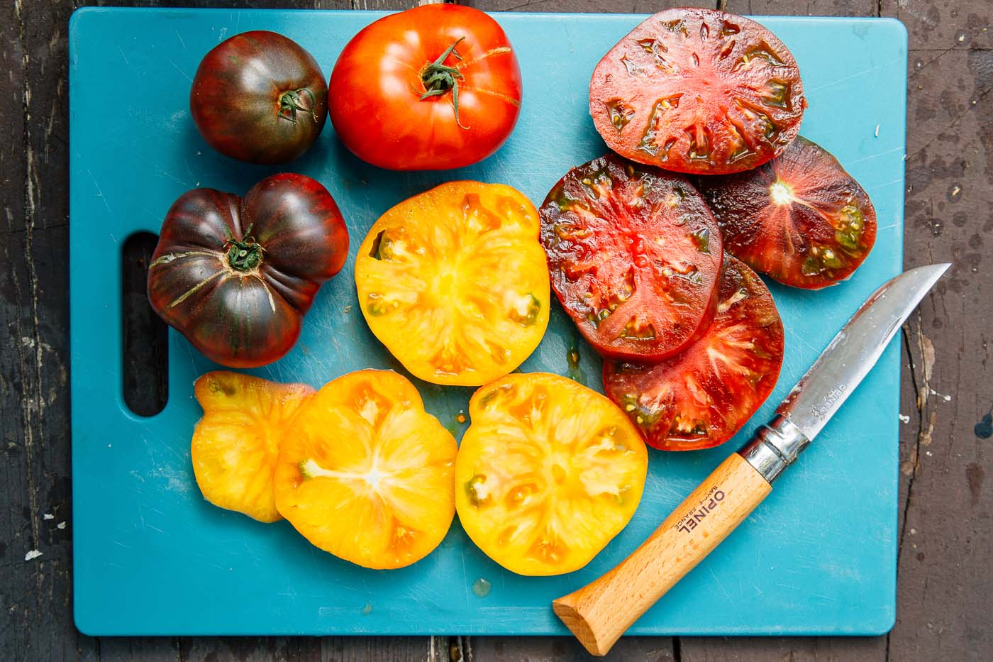Red and yellow heirloom tomato slices on a blue cutting board