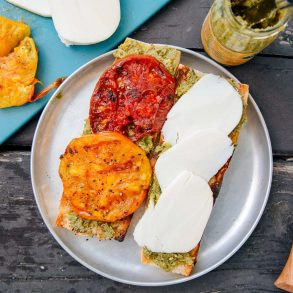 Grilled tomatoes and slices of cheese on a baguette