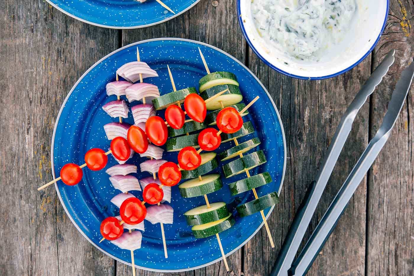 Tomatoes, red onion, and zucchini on skewers