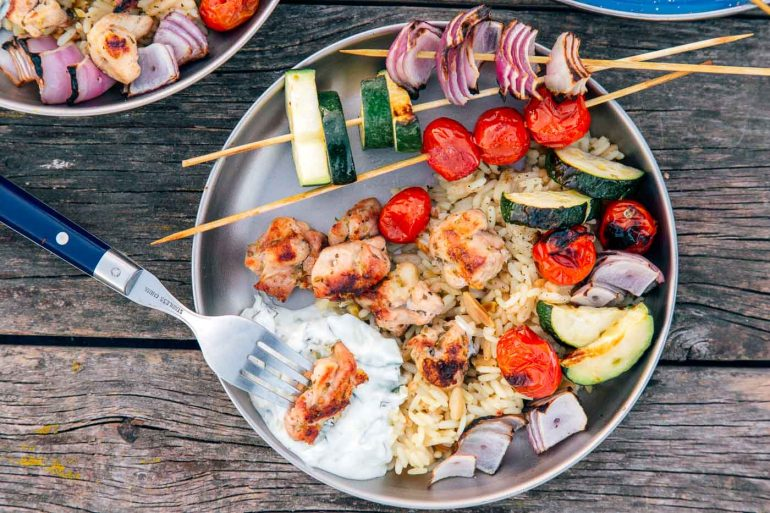 Chicken and vegetable skewers on a silver camping plate