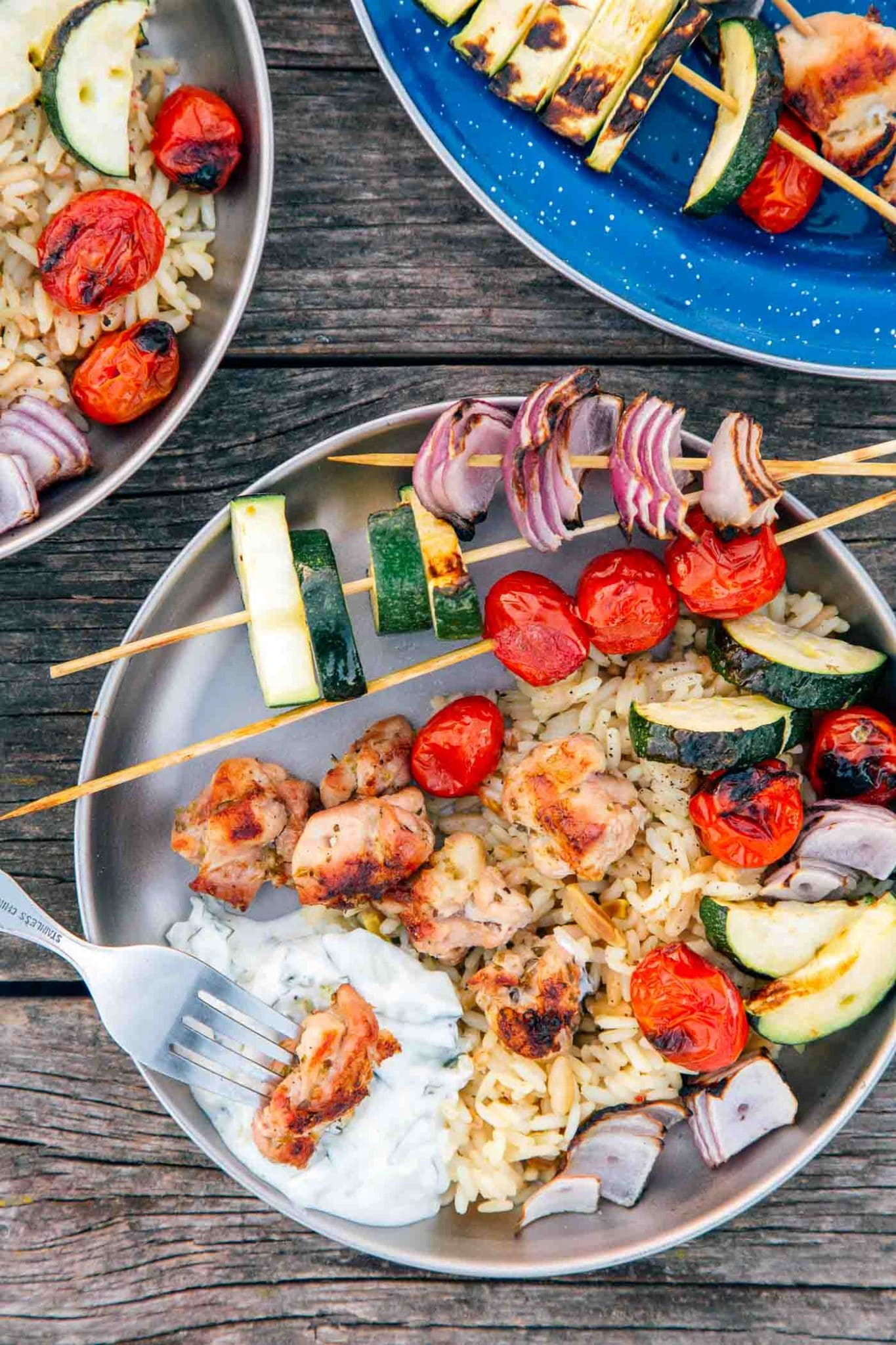 Grilled chicken and vegetable skewers with tzatziki sauce on a plate