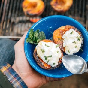 Two grilled peaches topped with yogurt in a blue bowl
