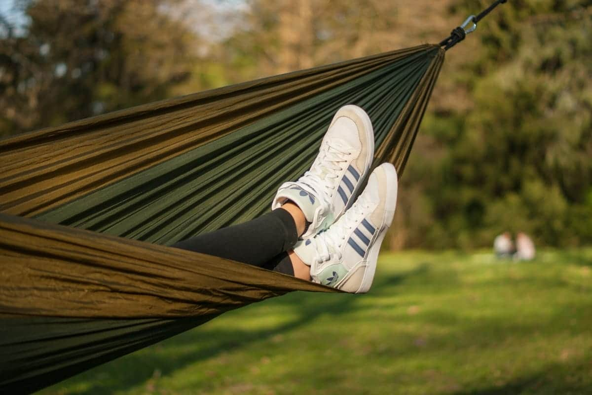 A green hammock with feet sticking out