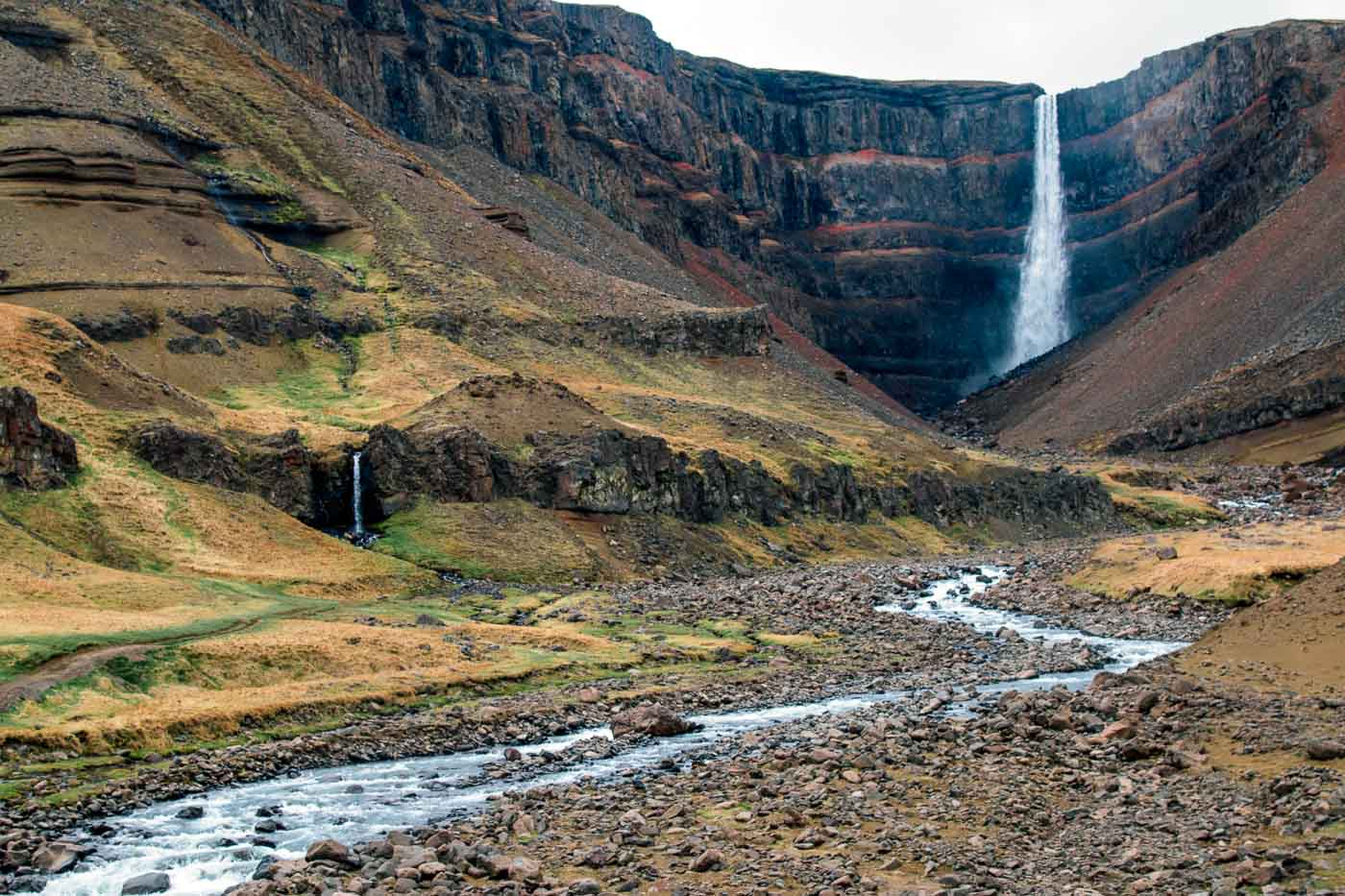 River flowing through a valley in front of the Hengifoss waterfall