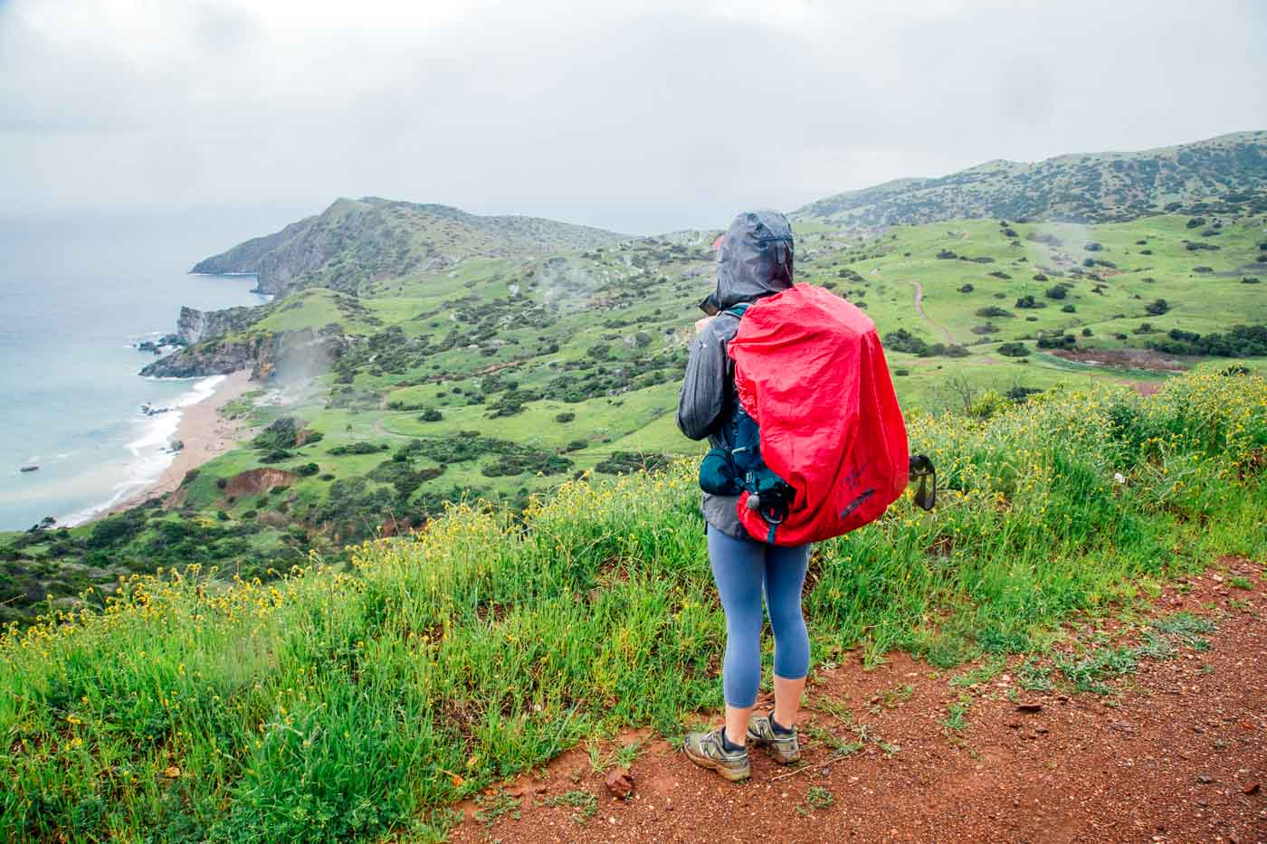 Woman on a trail overlook, looking out on the island and the ocean. The skies are rainy and she is wearing a rain jacket.