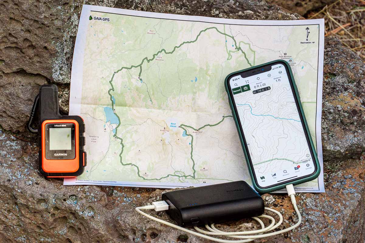 A paper map, satellite messenger, and phone with GPS