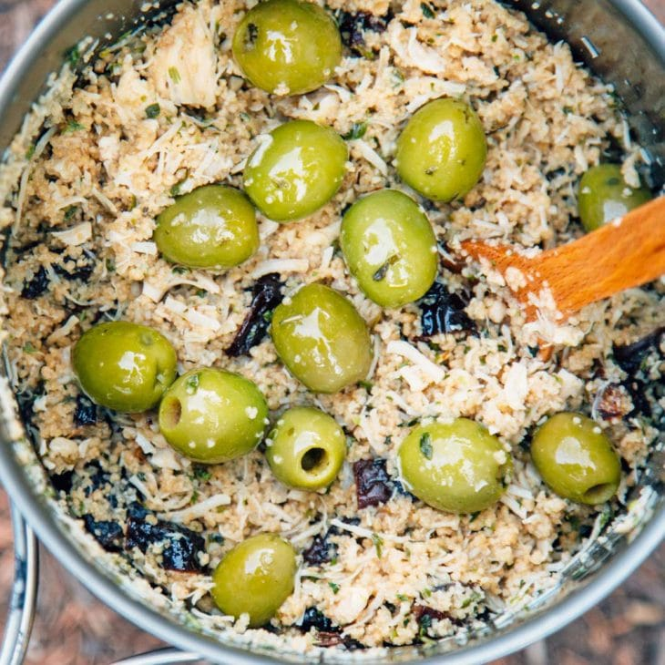 A pot with couscous, chicken, and green olives