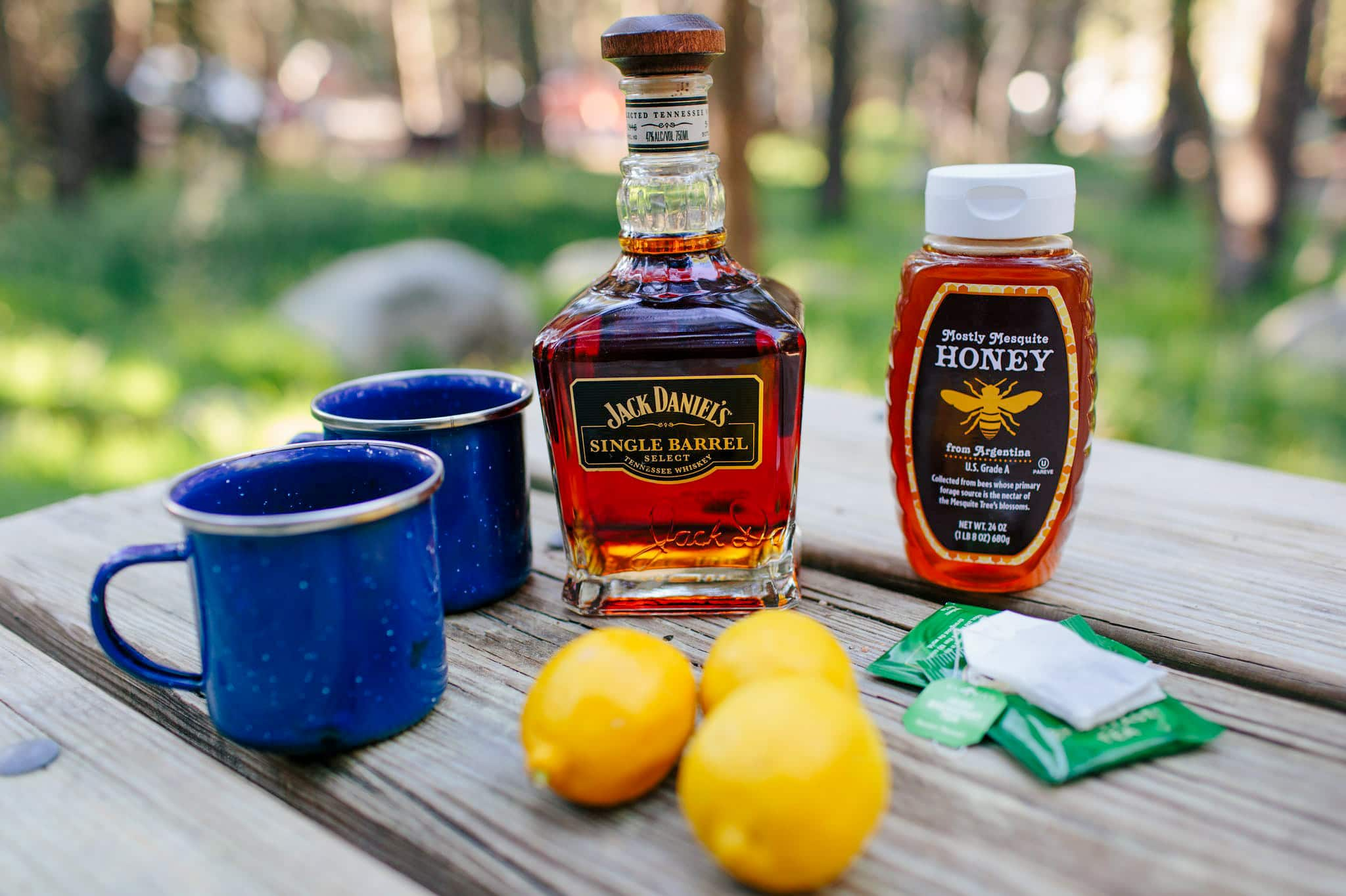 Hot Toddy ingredients: whiskey, honey, lemons, tea bag, on a camping table