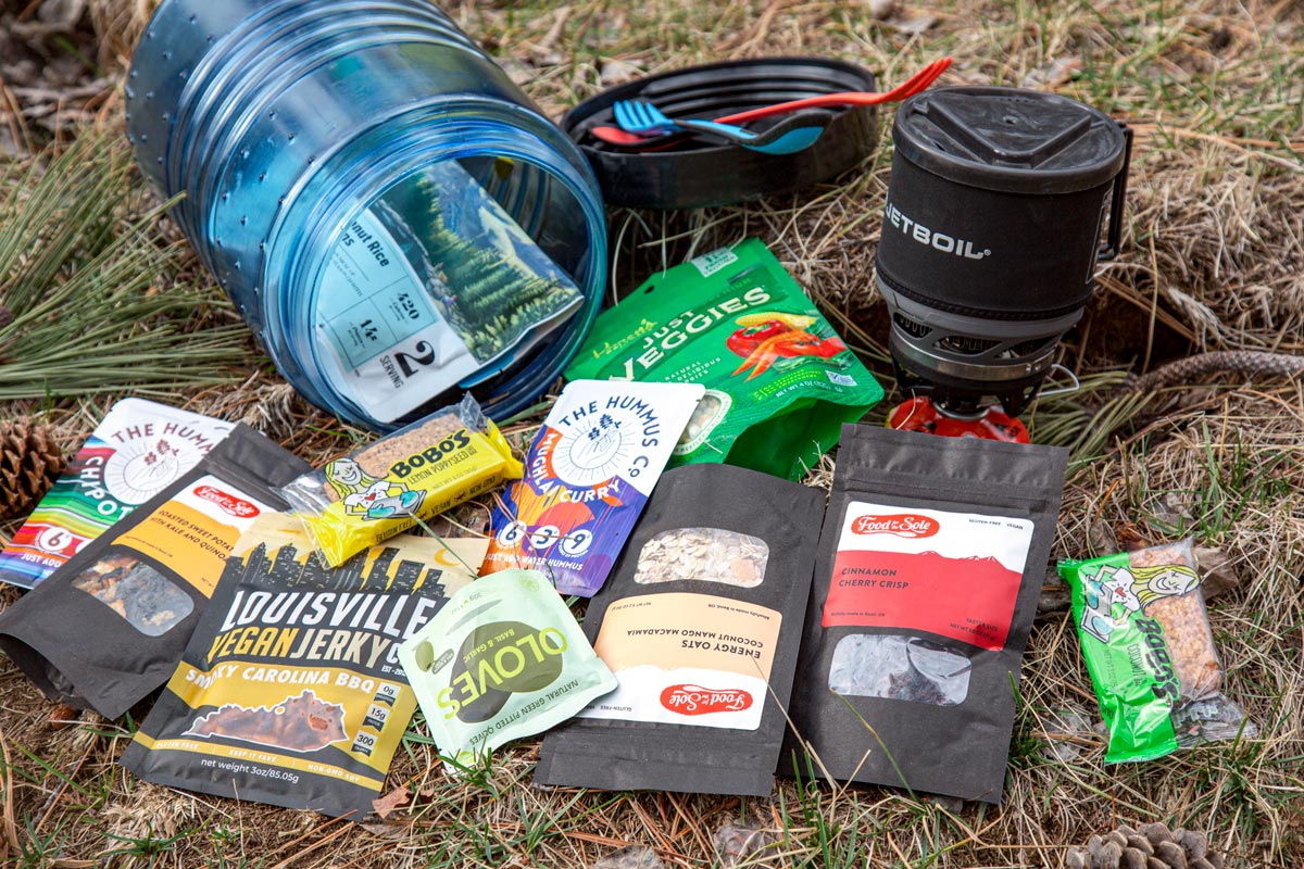 A bear canister with a spread of vegan backpacking meals