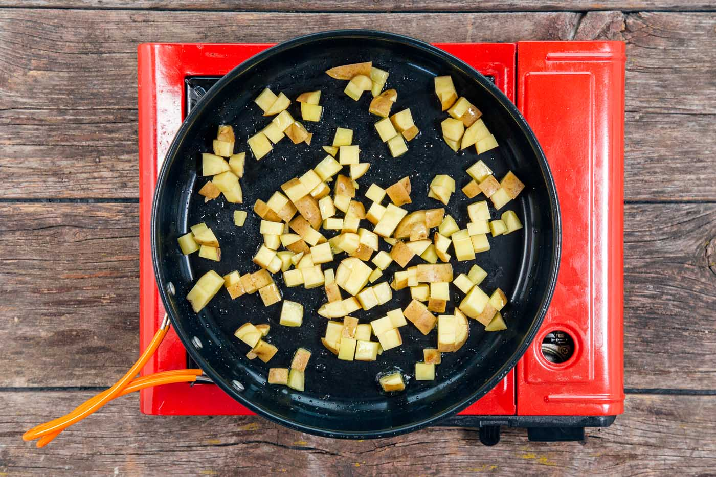 Cubed potatoes in a skillet for a breakfast scramble