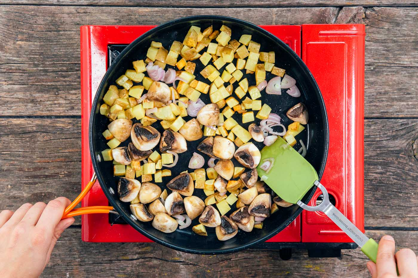 Sauteing cubed potatoes, quartered mushrooms, and shallots in a large skillet for a tofu scramble