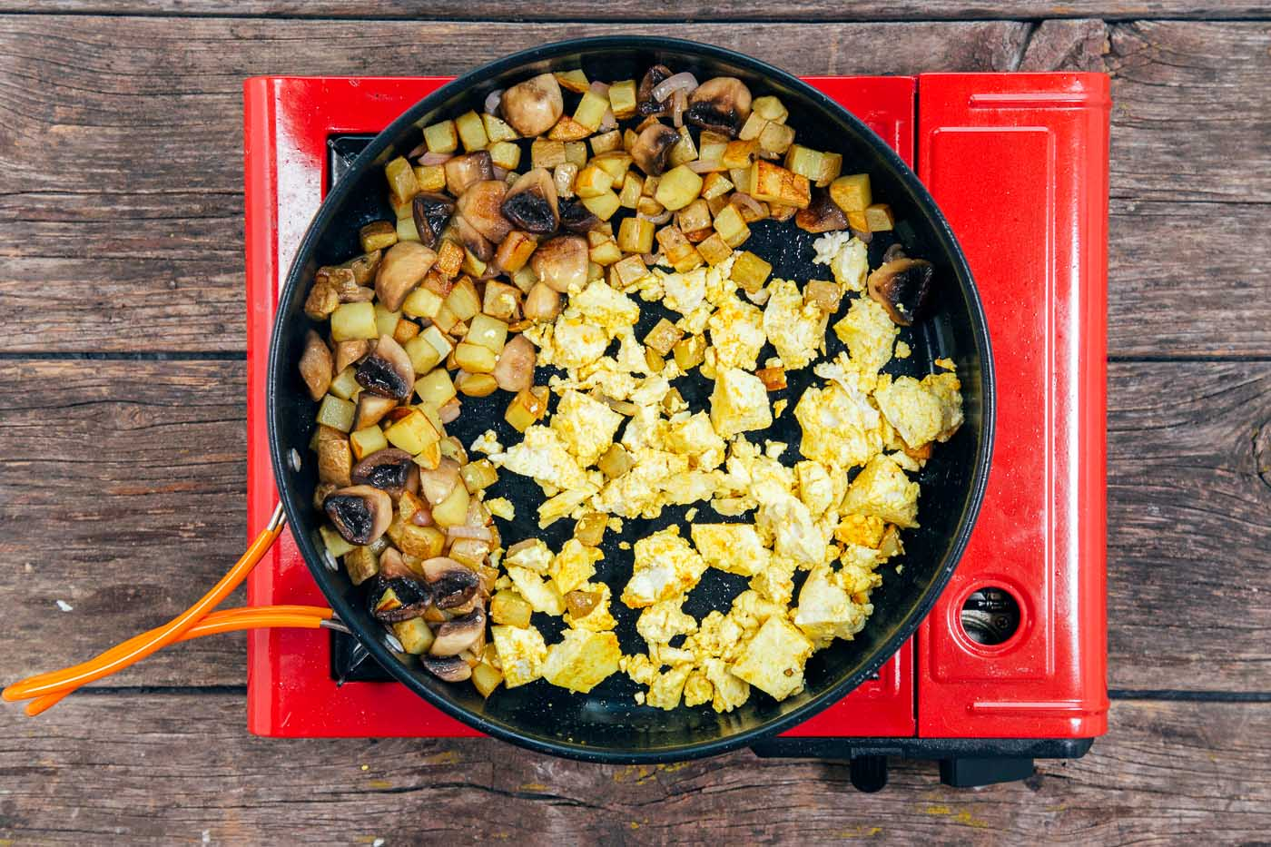 Cooking cubed potatoes and crumbled tofu in a large skillet for a scramble.