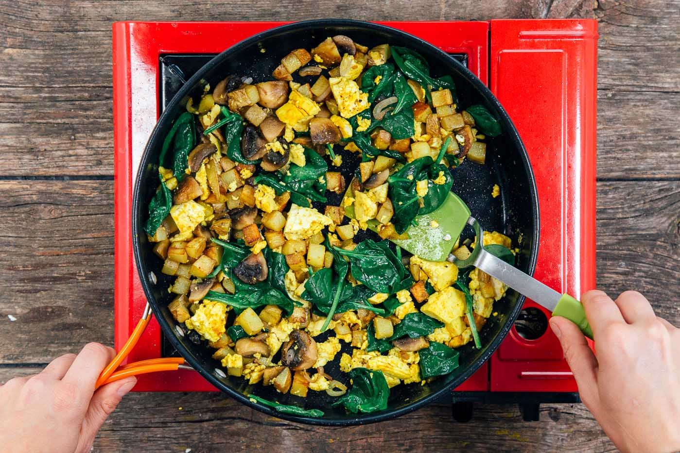 Cooking scrambled tofu with spinach in a large skillet on a camping stove