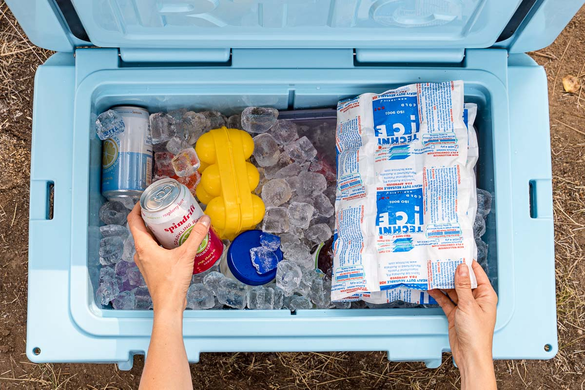 Hands reaching into a blue cooler full of ice to pick up a drink can