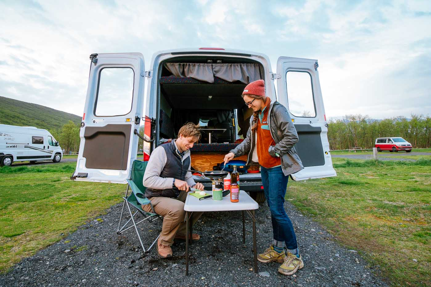A couple cooking in front of a camper van