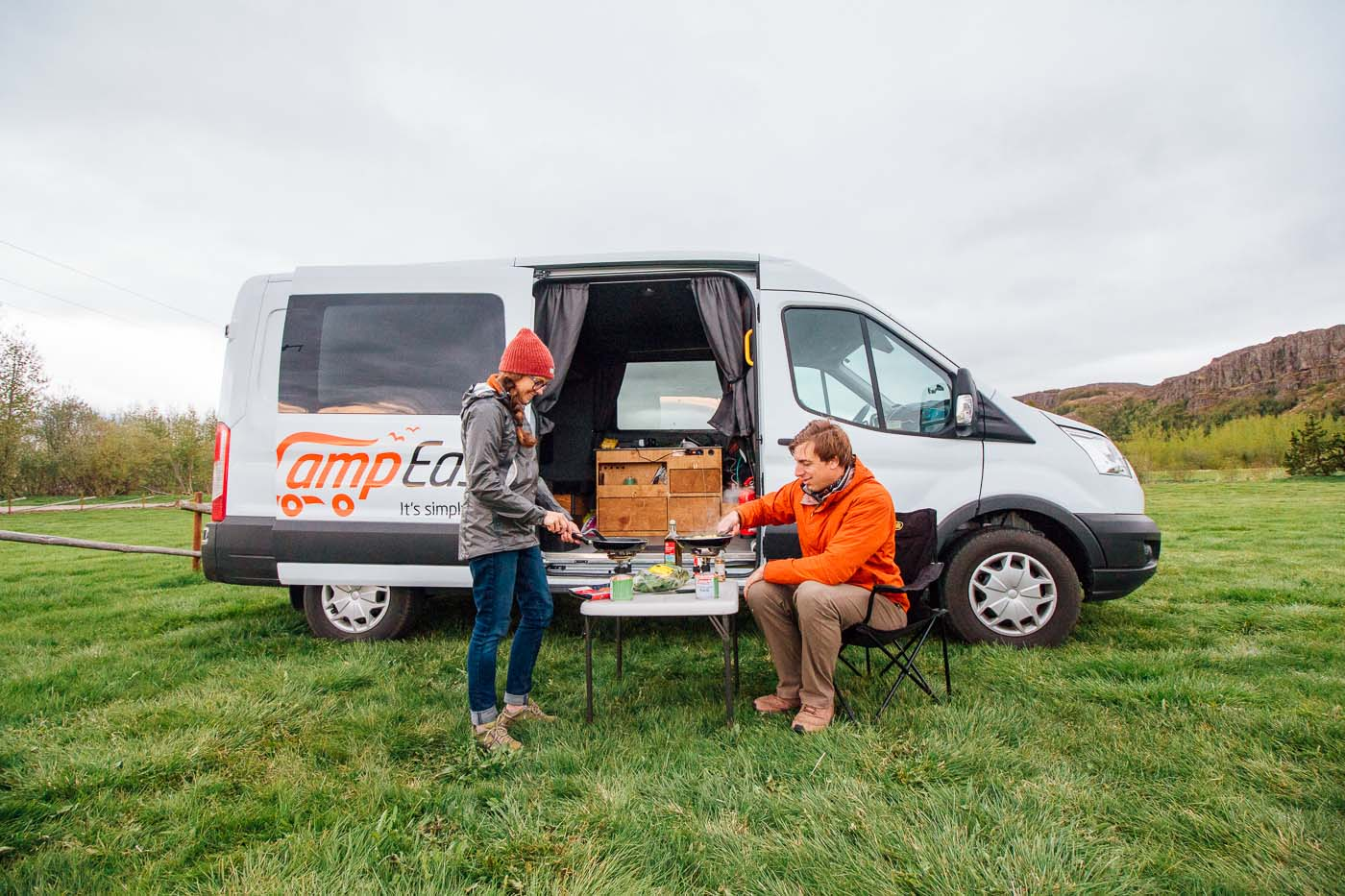 A couple cooking on a small table in front of a Camp Easy camper van in Iceland