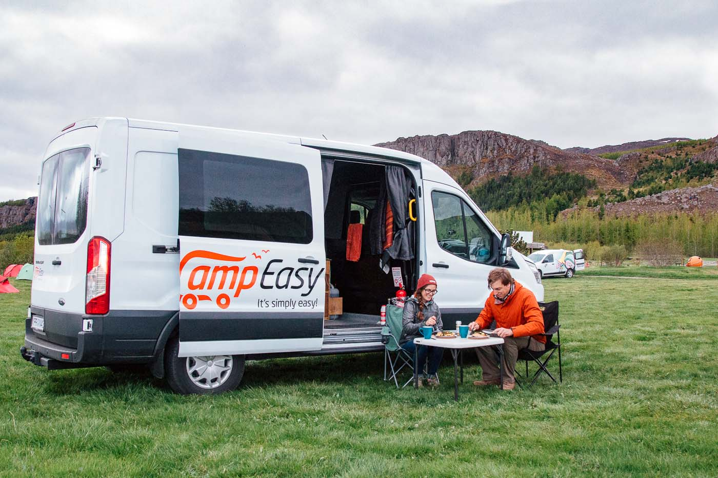 A couple eating a meal in front of a camper van