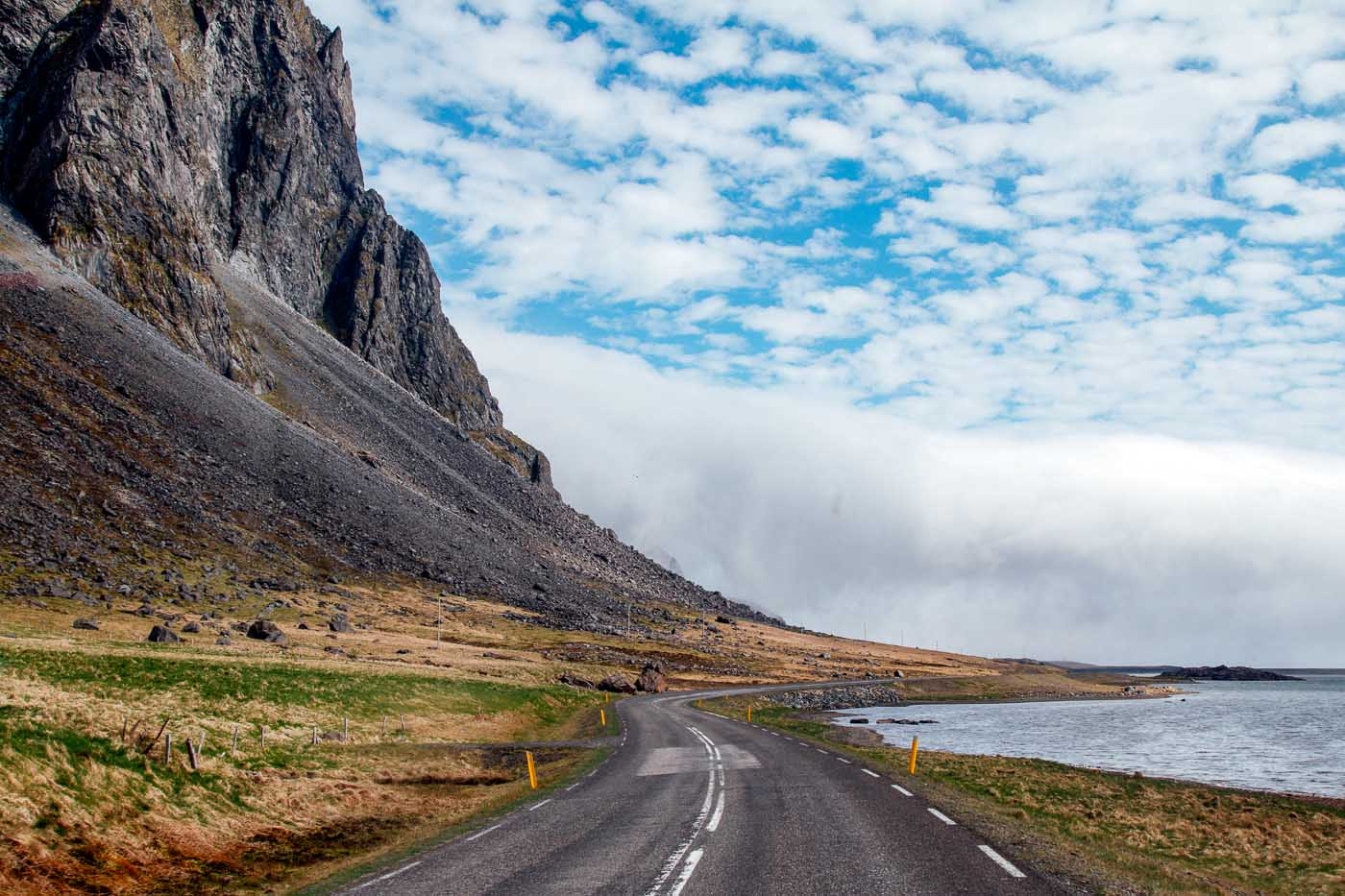 An empty road in Iceland. There are black mountains on the left and the ocean on the right.