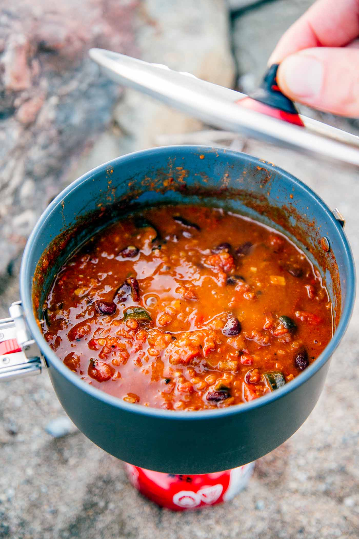 A backpacking pot full of red lentil chili.